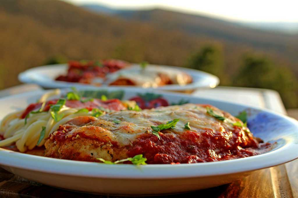 I practically drool just thinking about this delicious chicken parmesan. Lightly browned melted gooey cheese and fresh basil top these crispy breaded chicken breasts lying on a bed of tomato sauce with a side order of spaghetti. This is food that comforts the soul! | TheMountainKitchen.com
