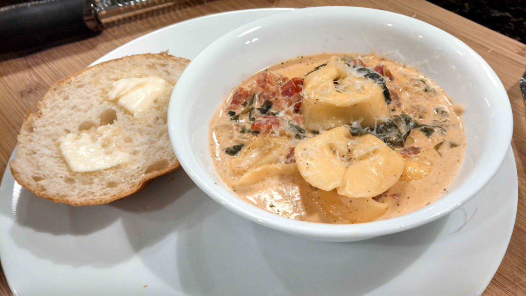 creamy tortelloni soup in a bowl with buttered bread on the side