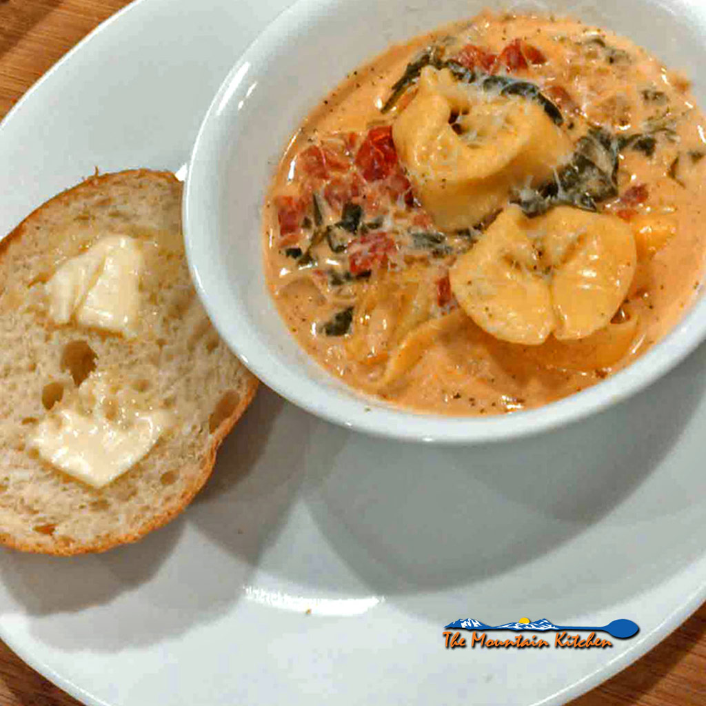 This quick and easy creamy tortelloni soup is filled with cheese tortelloni and fresh spinach. The ultimate comfort food for what ails ya! | TheMountainKitchen.com