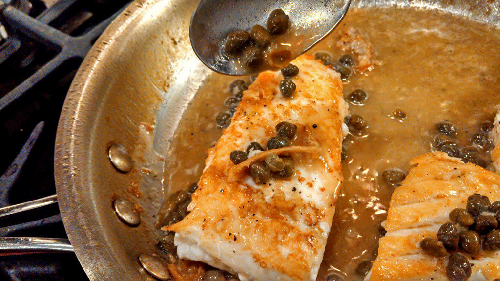 pouring the pan sauce over fish in skillet