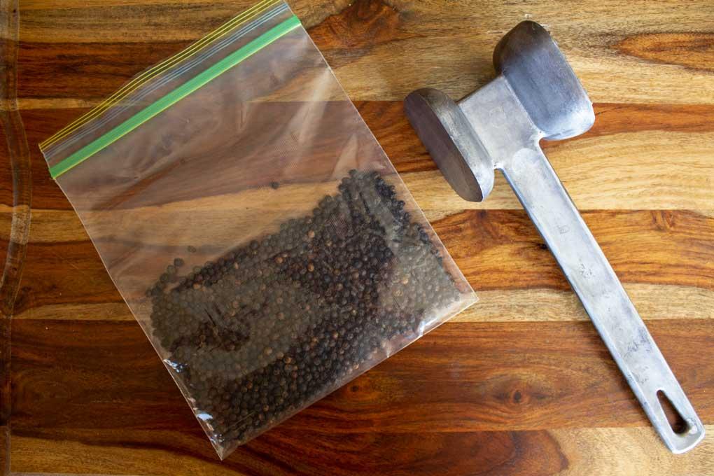 peppercorns with mallet for lemon pepper seasoning