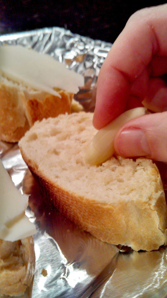 rubbing garlic onto bread