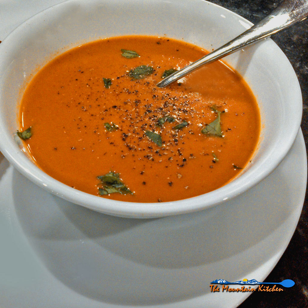 This vibrant roasted tomato red pepper soup made of red bell peppers and vine ripened tomatoes, roasted and combined together to satisfy the senses. | TheMountainKitchen.com