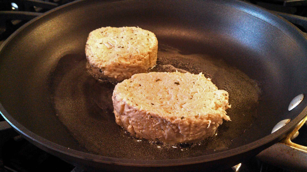 crab cakes cooking in skillet