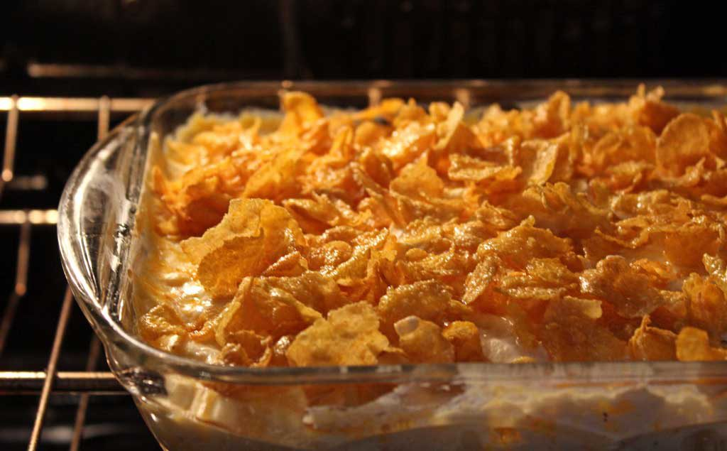 Hash Brown Potato Casserole: hash brown potatoes and onions, mixed in a creamy sour cream and cheese mixture, baked and topped with buttery corn flakes. | TheMountainKitchen.com