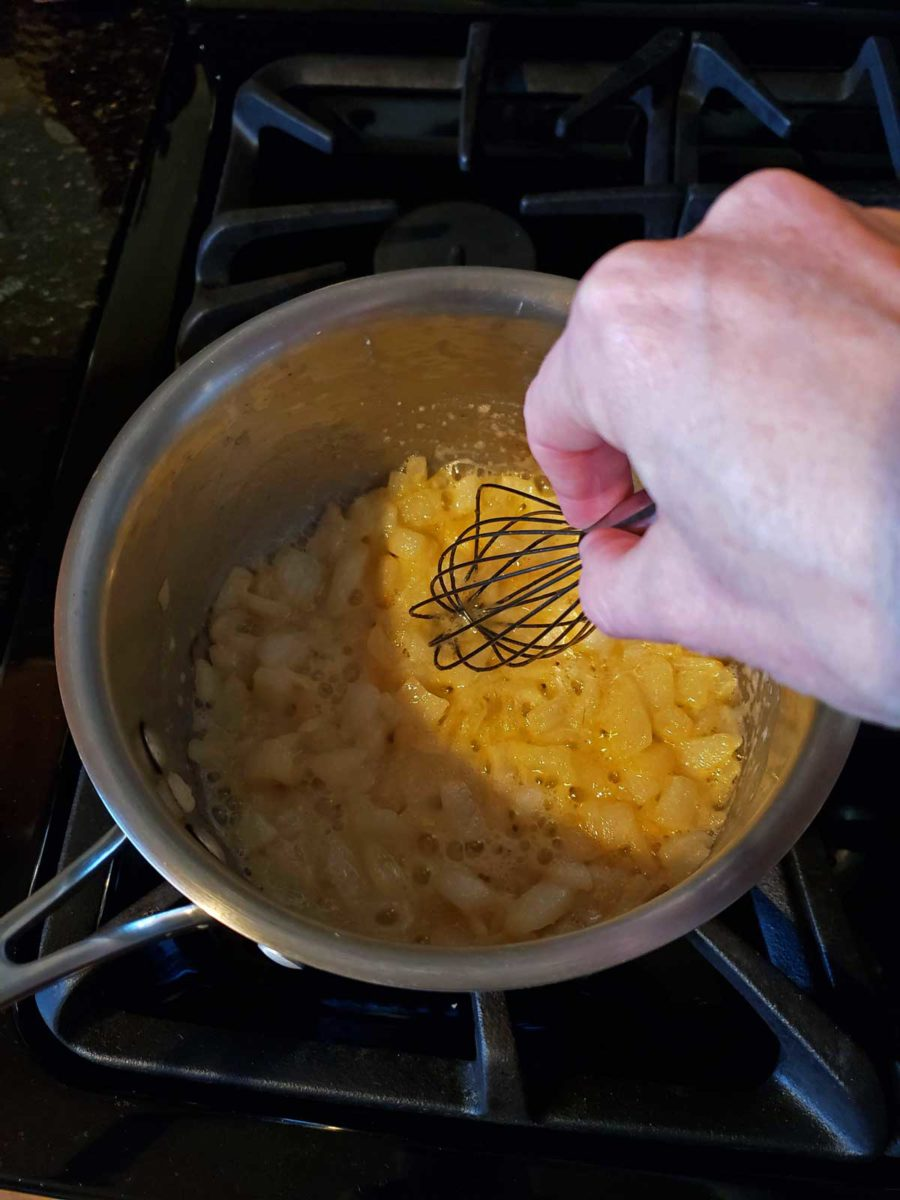 whisking onions in a pot