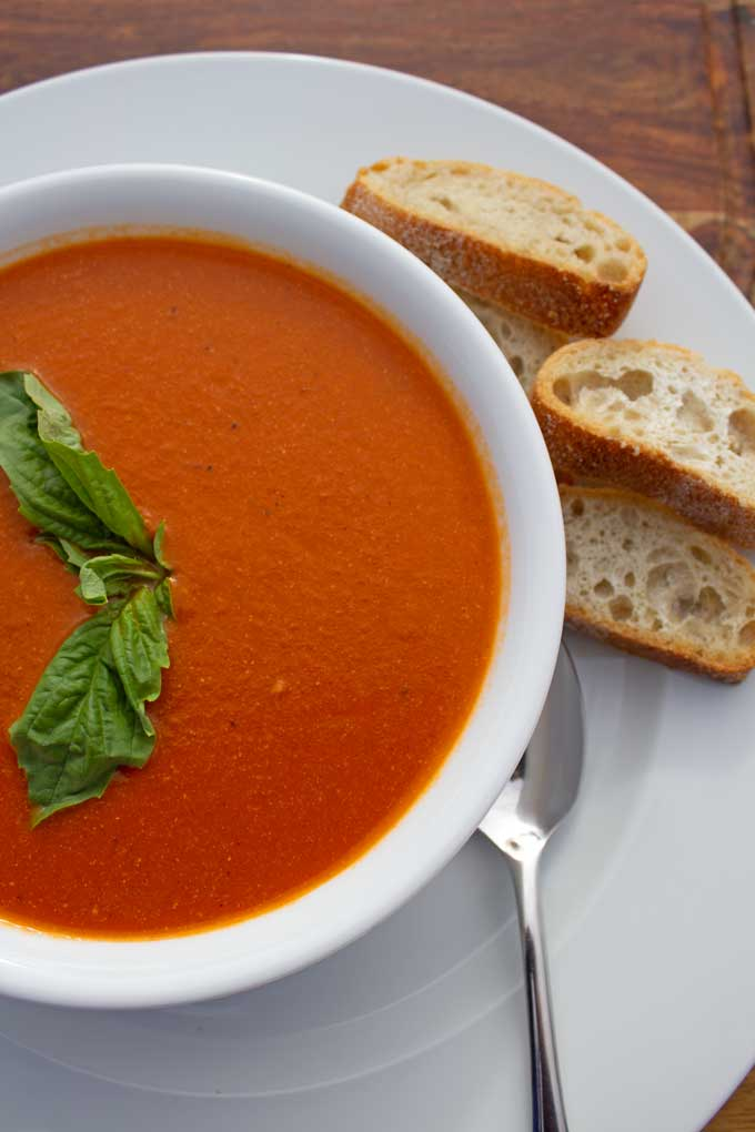 This delicious roasted tomato soup combines roasted tomatoes, carrots and onions with vegetable broth to simmer before blending it into a silky smooth soup.