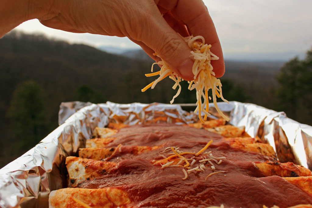 sprinkling cheese on top of enchiladas
