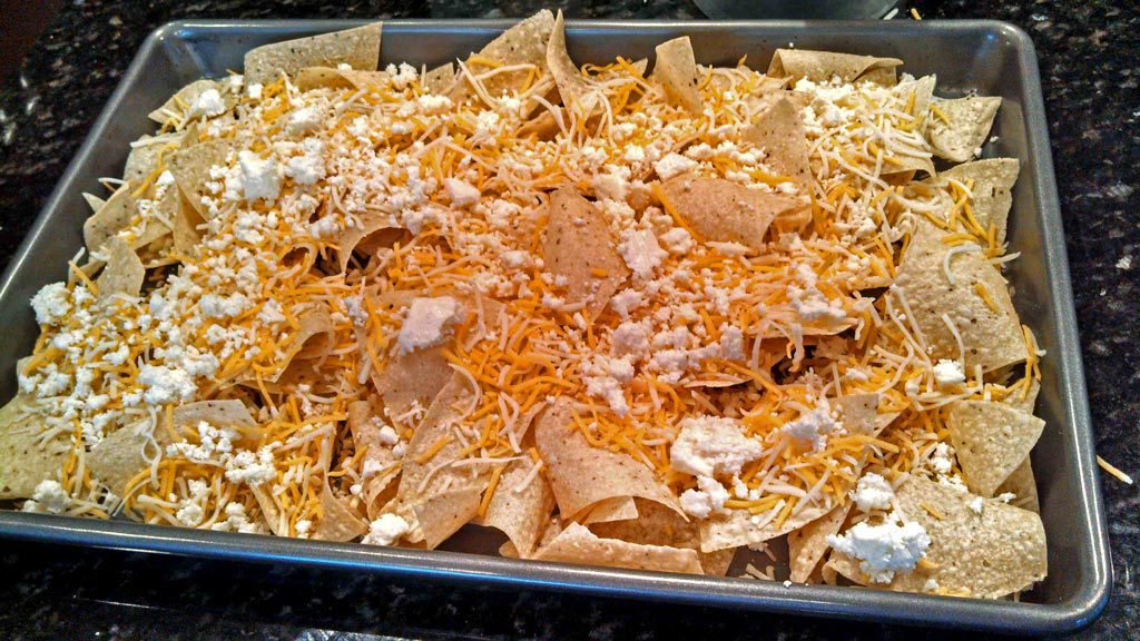 tortilla chips and cheese on a baking sheet