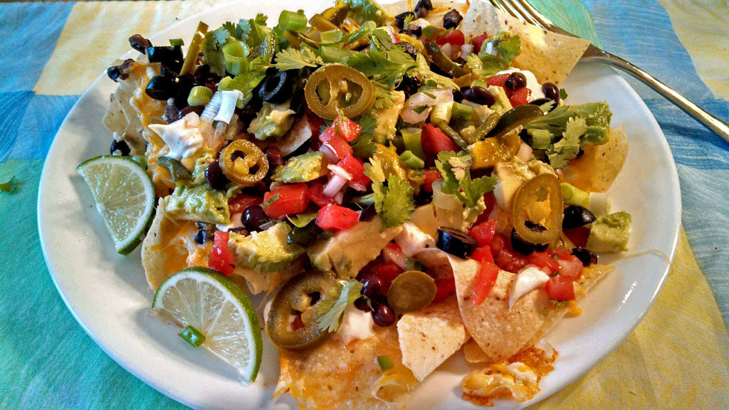 These vegetarian nachos can be made with tortilla chips covered in cheeses, black beans and any meatless toppings you choose. A quick, easy meatless meal! | TheMountainKitchen.com
