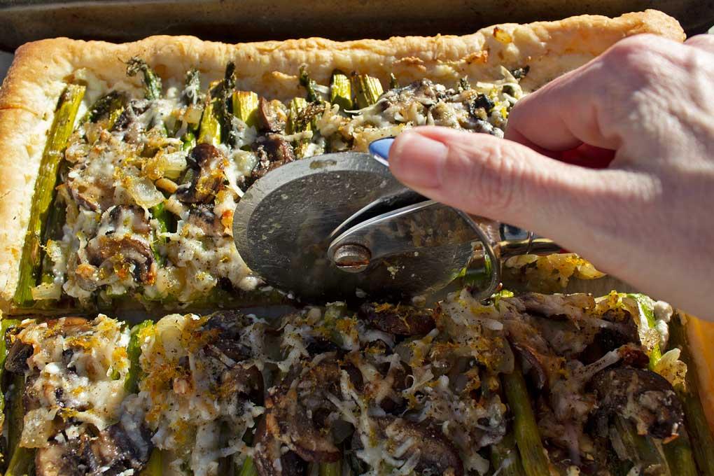 cutting asparagus-ricotta tart with pizza cutter