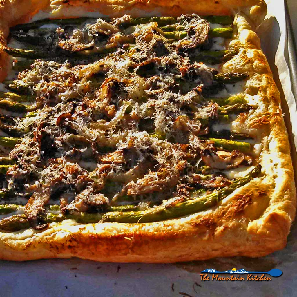 This asparagus ricotta tart is made of puff pastry, ricotta topped with asparagus, mushrooms and onions, and parmesan cheese. Great for Meatless Monday! | TheMountainKitchen.com