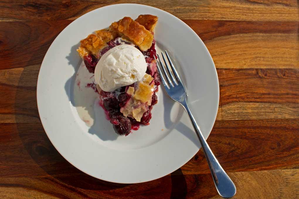 slice of homemade cherry pie with scoop of ice cream