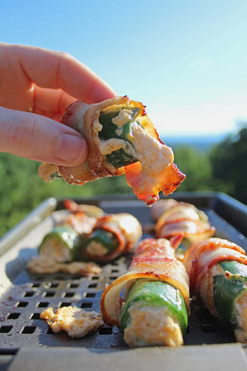 These grilled bacon wrapped jalapeño poppers are stuffed with two different kinds of cheese, wrapped in bacon and grilled until crispy and bursting with flavor! #jalapenopoppers #grilled #bacon #summer #grilling #recipes
