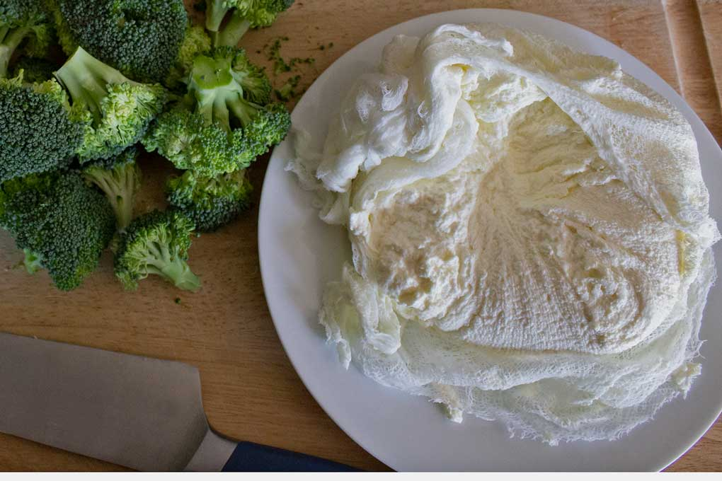 ricotta cheese in cheesecloth on cutting board with broccoli