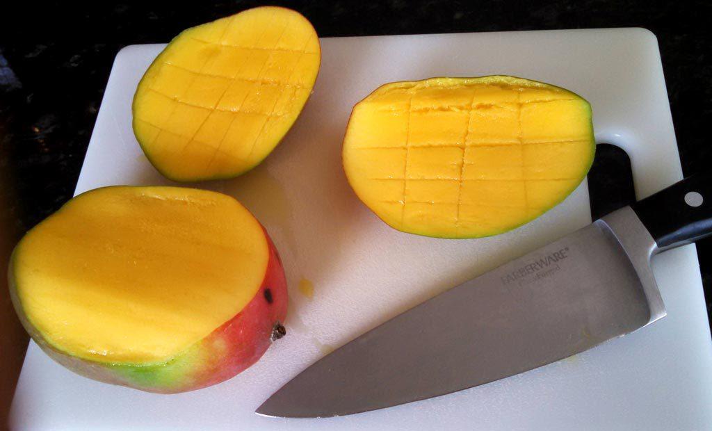 cut mango on cutting board with knife