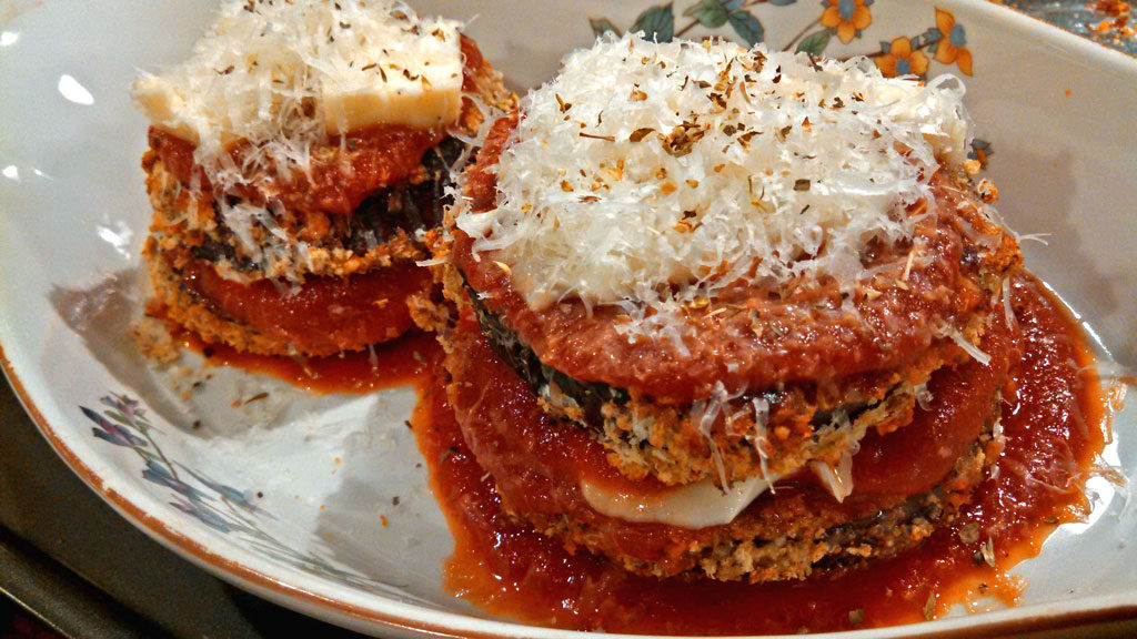 Healthy Oven-Baked Eggplant Parmesan ~ Delicate eggplant slices lightly breaded and oven-baked with tangy tomato sauce, layered with gooey browned cheese. | TheMountainKitchen.com