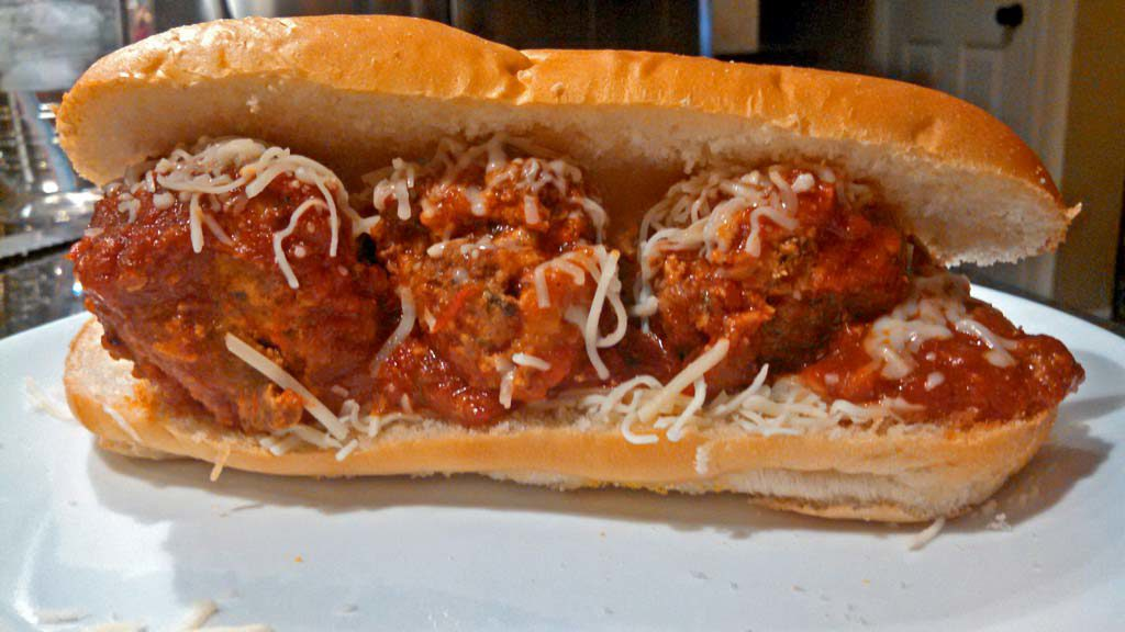 These Meatball Sandwiches have juicy meatballs simmered in thick warm marinara sauce, placed onto a bun, topped with mozzarella and parmesan cheeses. | TheMountainKitchen.com