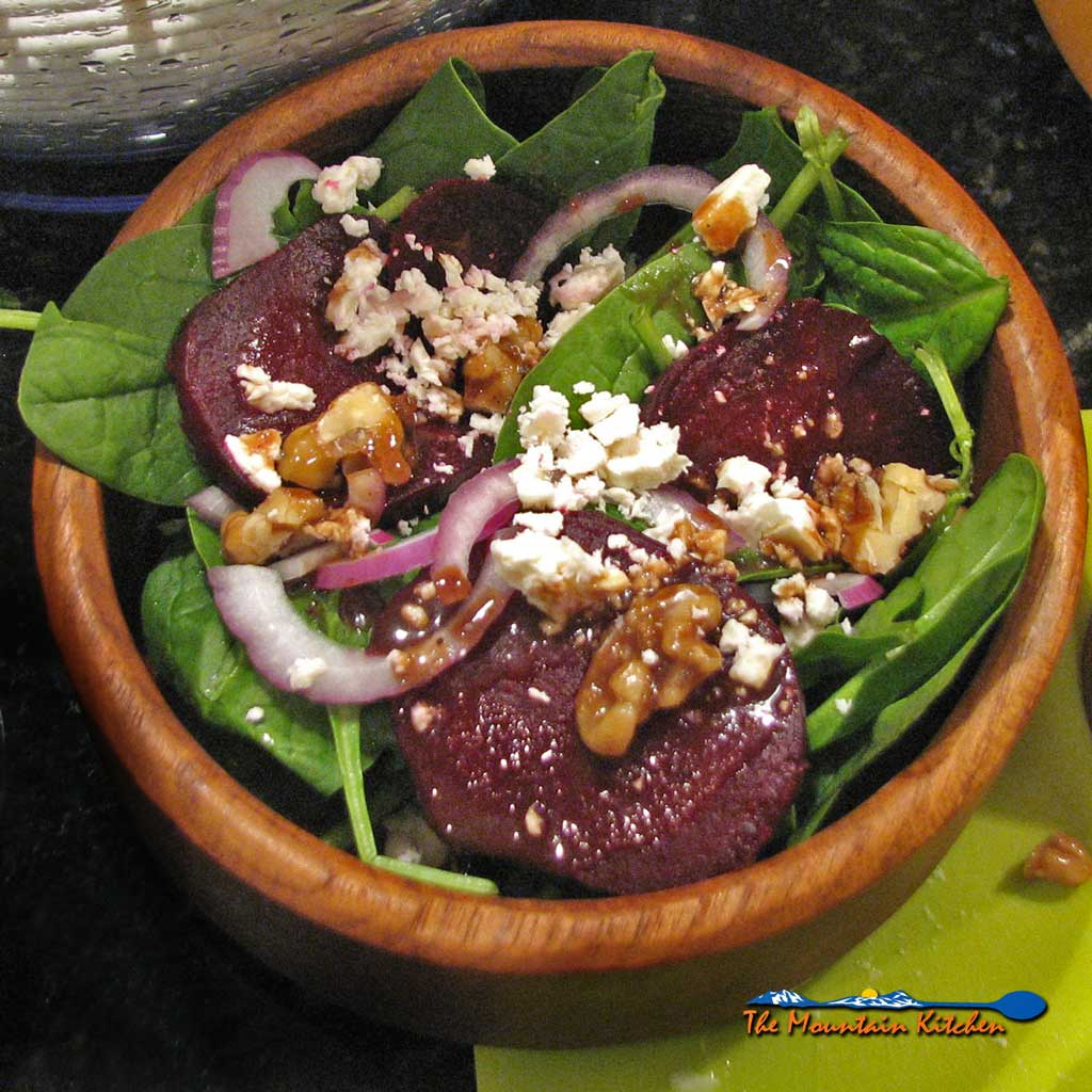 This roasted beet salad with fresh spinach, feta cheese, slices of red onion and candied walnuts, drizzled with balsamic maple cinnamon dressing. | TheMountainKitchen.com