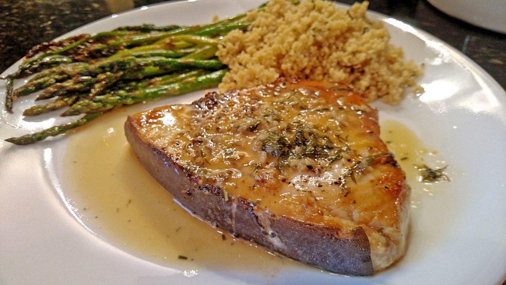 Sexy swordfish fillets smothered in a wonderful zesty sauce made of white wine, chicken broth, and garlic then finished off with lemon and fresh herbs. | TheMountainKitchen.com
