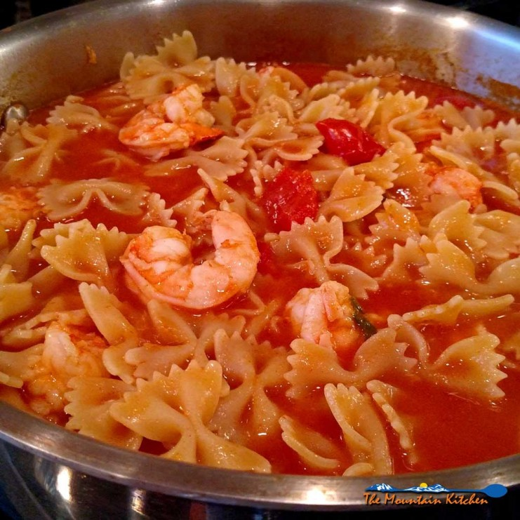 Basil, garlic, broth and tomato sauce all come together to create a delicious light sauce over Farfalle noodles and plump shrimp for this Shrimp Pomodoro. | TheMountainKitchen.com