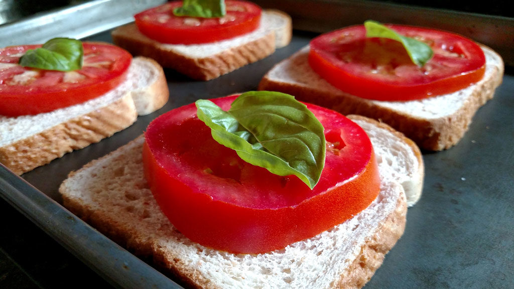 basil and tomato slices on top of slices of bread
