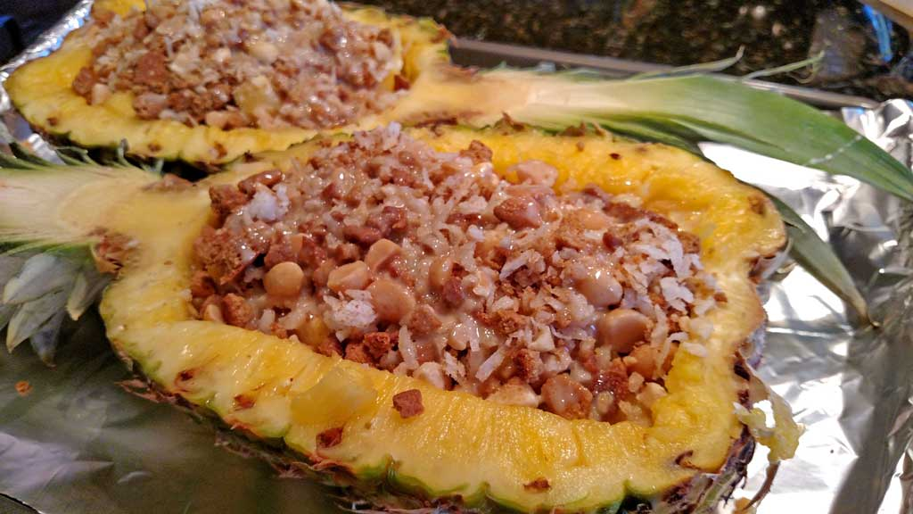 This stuffed pineapple is a tropical paradise,. Juicy pineapple baked and caramelized with a coconut, ginger snap topping.   TheMountainKitchen.com
