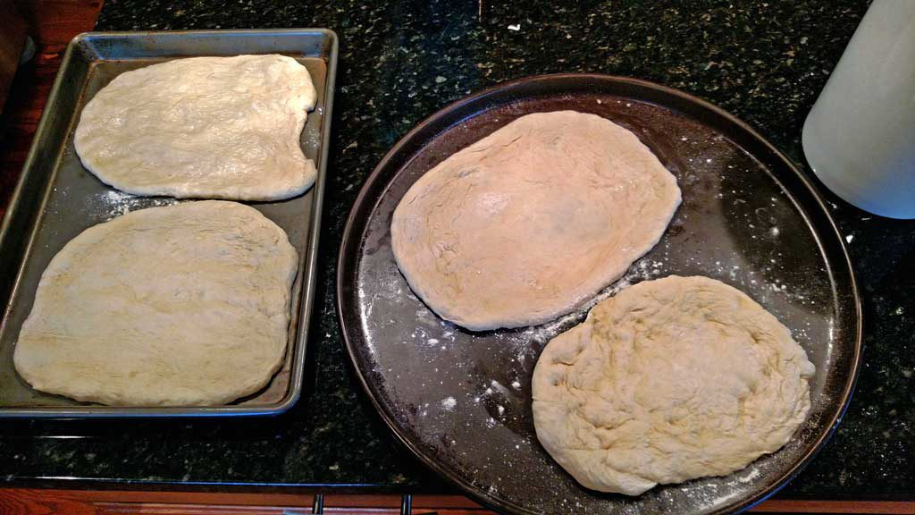 Pizza dough laid out on baking sheets ready for the grill.