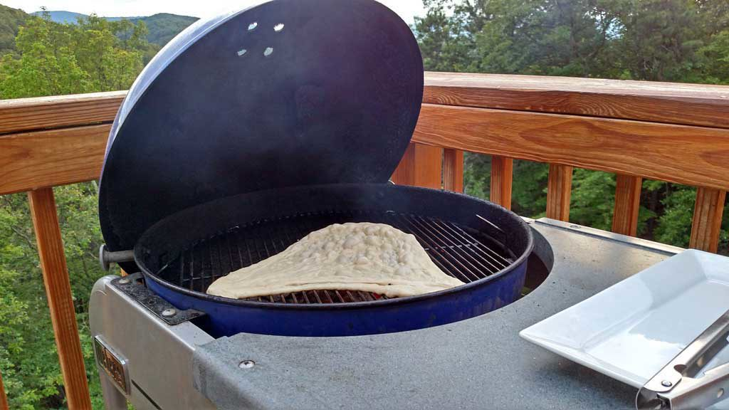 Pizza dough grilling on the Weber charcoal grill.