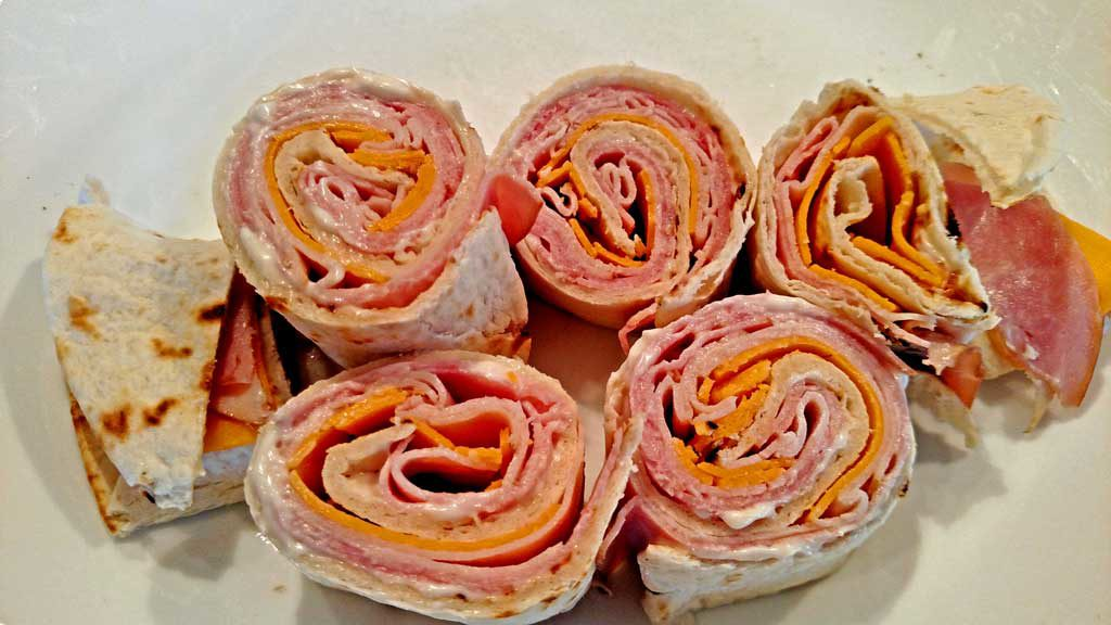 Salsa club rollups are flour tortillas rolled up with ham and cheese; sliced into mini rolls, served with shredded lettuce, salsa, sour cream and chives. | TheMountainKitchen.com