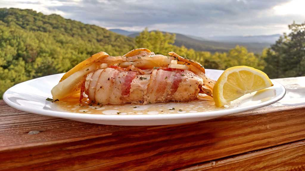 Easy baked Mahi Mahi is oven baked enclosed in a packet that locks in moisture and flavor cooked with potatoes, onions, lemon, slices and bacon. | TheMountainKitchen.com