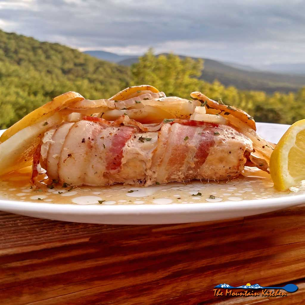 Easy baked Mahi Mahi is oven baked enclosed in a packet that locks in moisture and flavor cooked with potatoes, onions, lemon, slices and bacon.