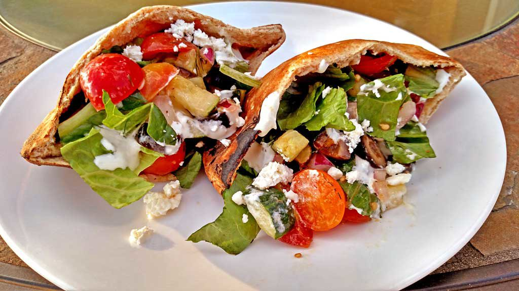 Greek pita sandwiches with toasted pita bread stuffed with a Greek Salad marinated in Greek Dressing, with fresh greens and a tangy whipped feta dip. | TheMountainKitchen.com