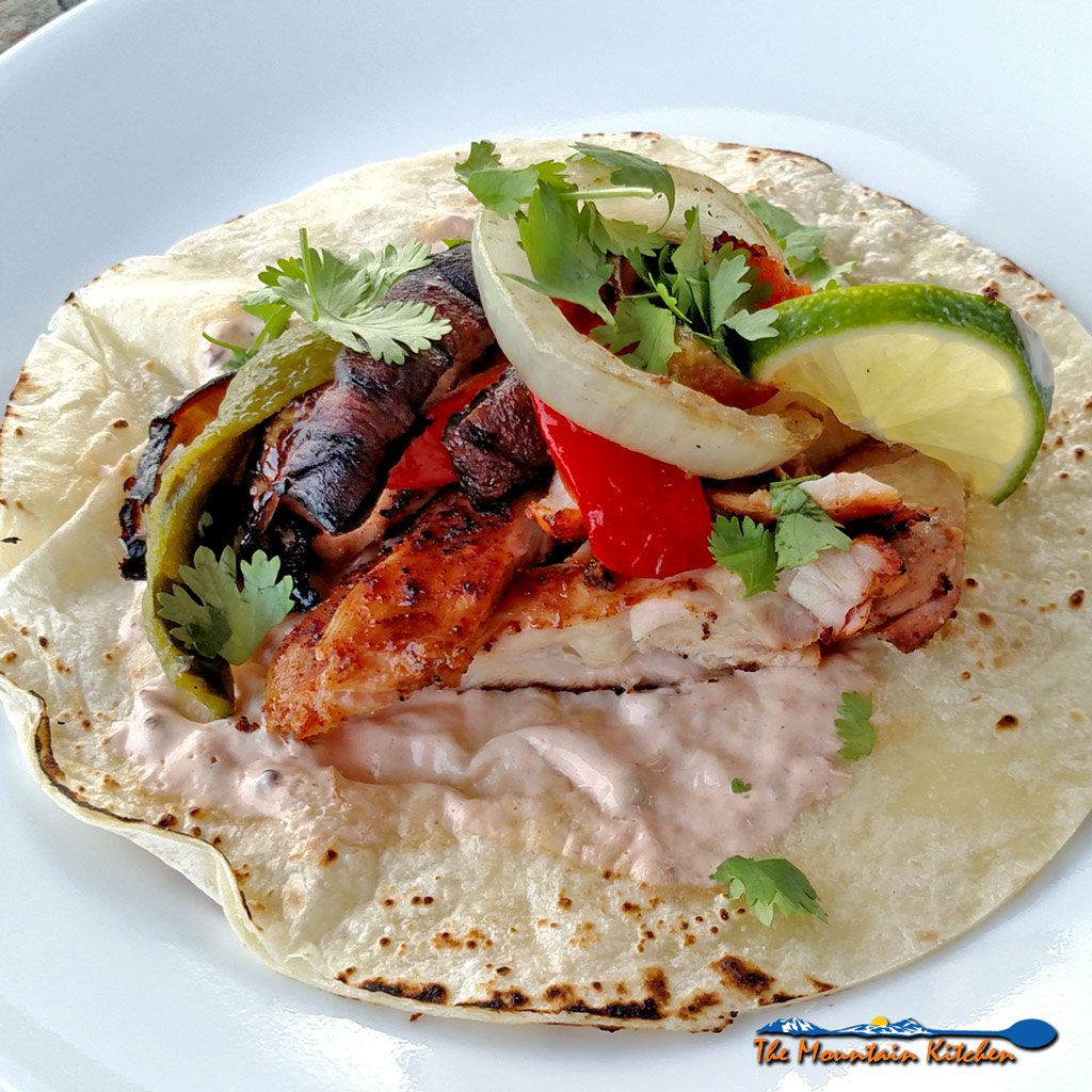 These delicious grilled chicken fajitas are a breeze to make with grilled chicken thighs with Mexican spices served with grilled vegetables on a tortilla. | TheMountainKitchen.com