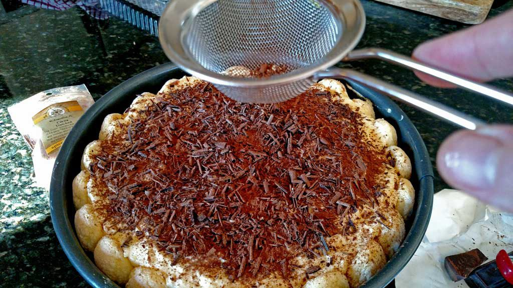 dusting top of homemade tiramisu with coco powder and chocolate shavings