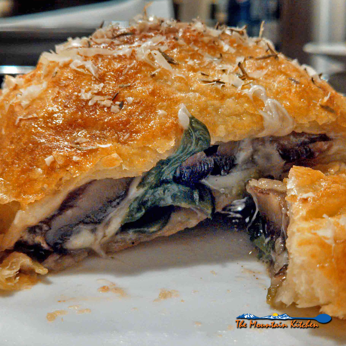 This recipe is a spin-off the classic Beef Wellington recipe, this vegetarian version uses Portobello mushroom caps, spinach and cheese stuffed inside of a flaky pastry crust. | TheMountainKitchen.com