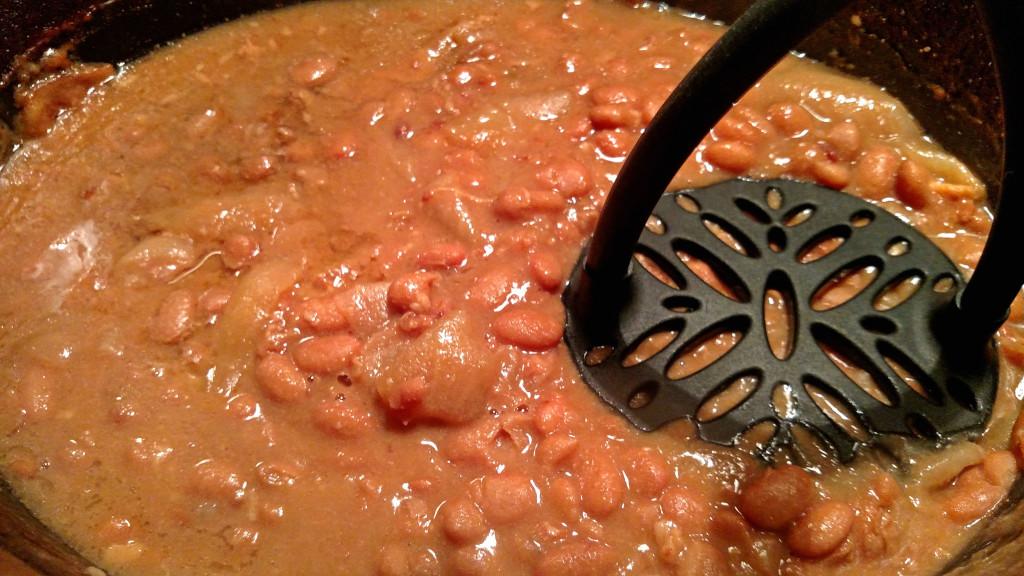 mashing refried beans with potato masher