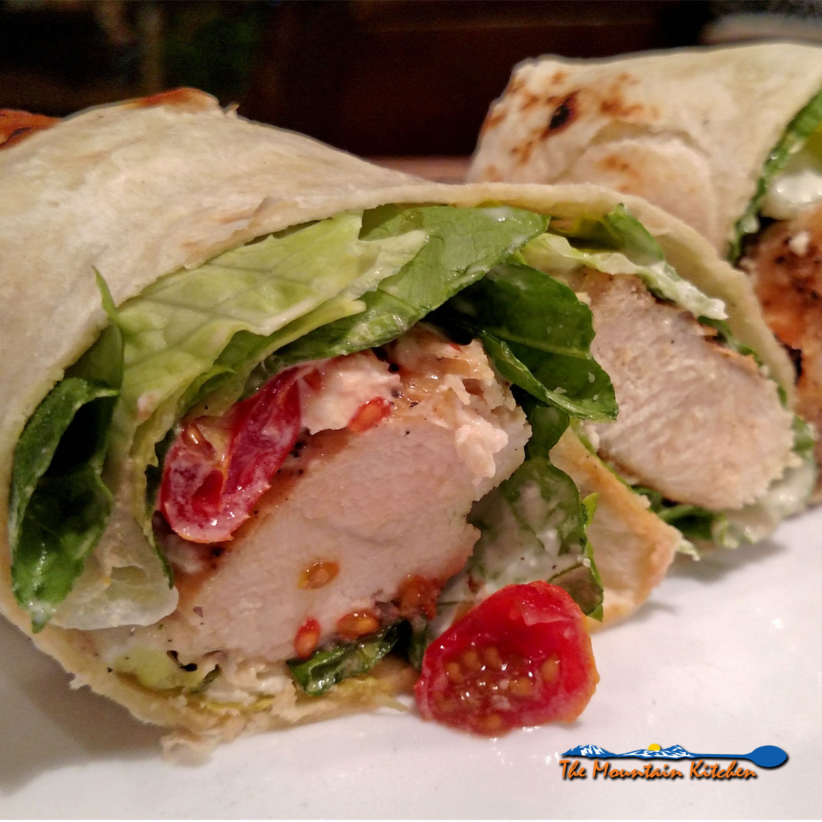 Chicken Caesar Wraps made of juicy chicken, wrapped in a tortilla with lettuce, tomatoes, feta, and parmesan cheeses, and crispy pepperoni.
