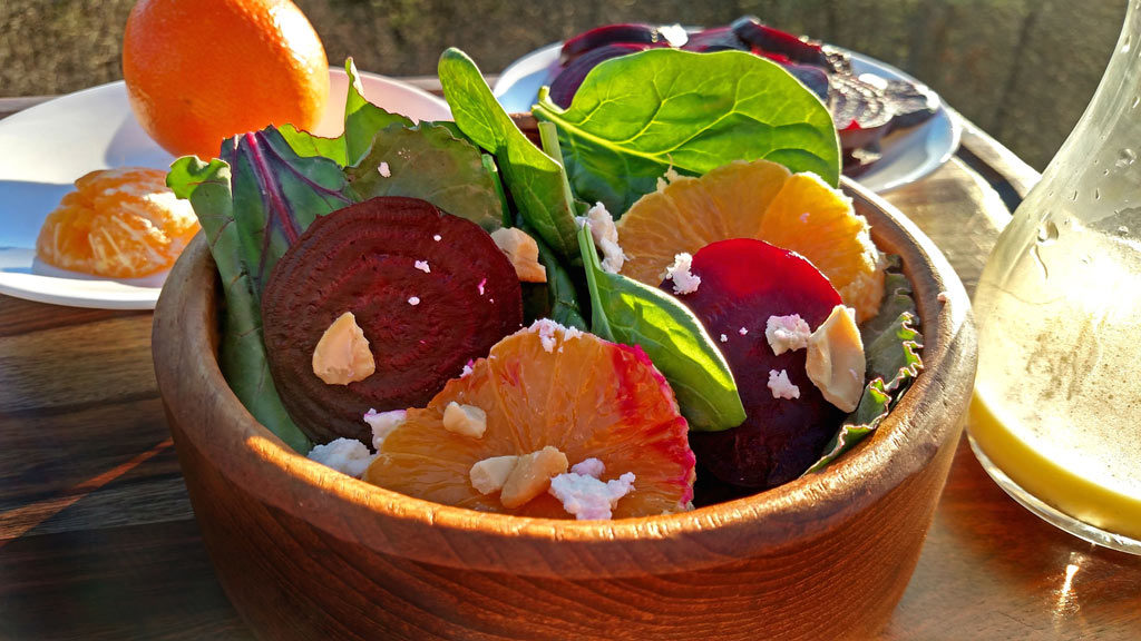This roasted beet citrus salad is guaranteed to brighten up any winter day! roasted beets, tangelos, feta cheese, cashews on a bed baby spinach. | TheMountainKitchen.com
