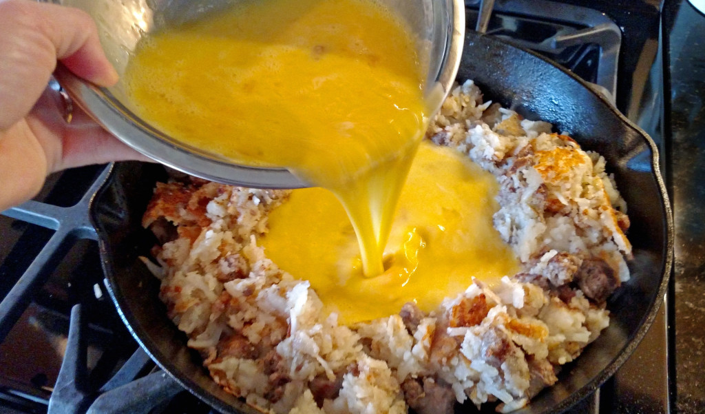 pouring the eggs into the camper's breakfast hash