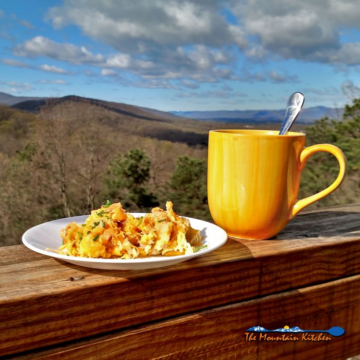 Camper's Breakfast Hash on a plate with cup of coffee and mountain view
