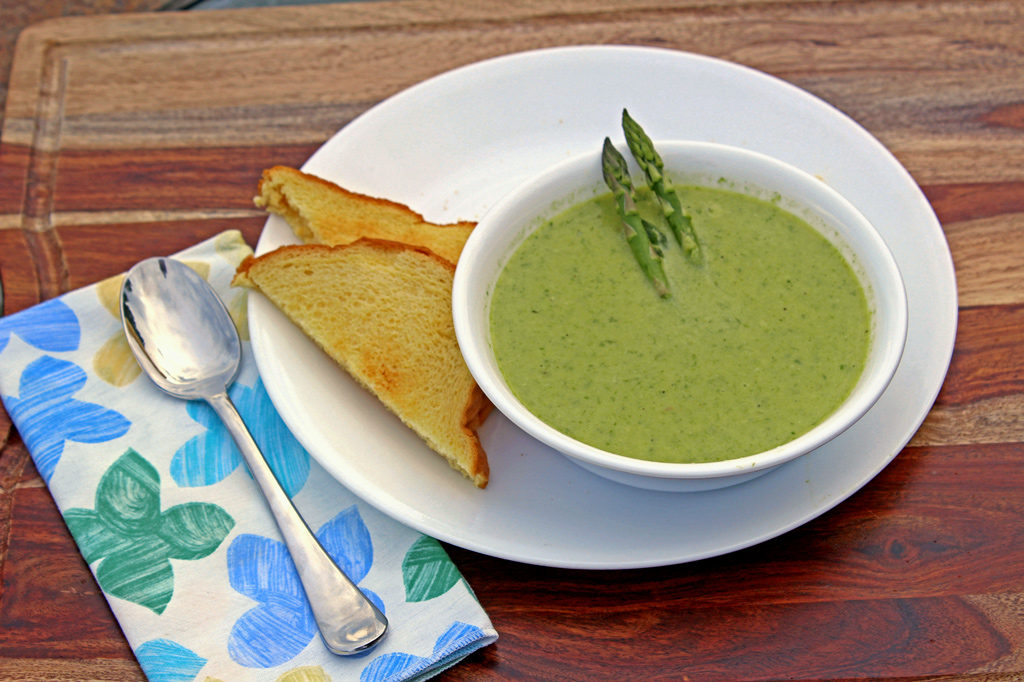 cream of asparagus soup in bowl with toast