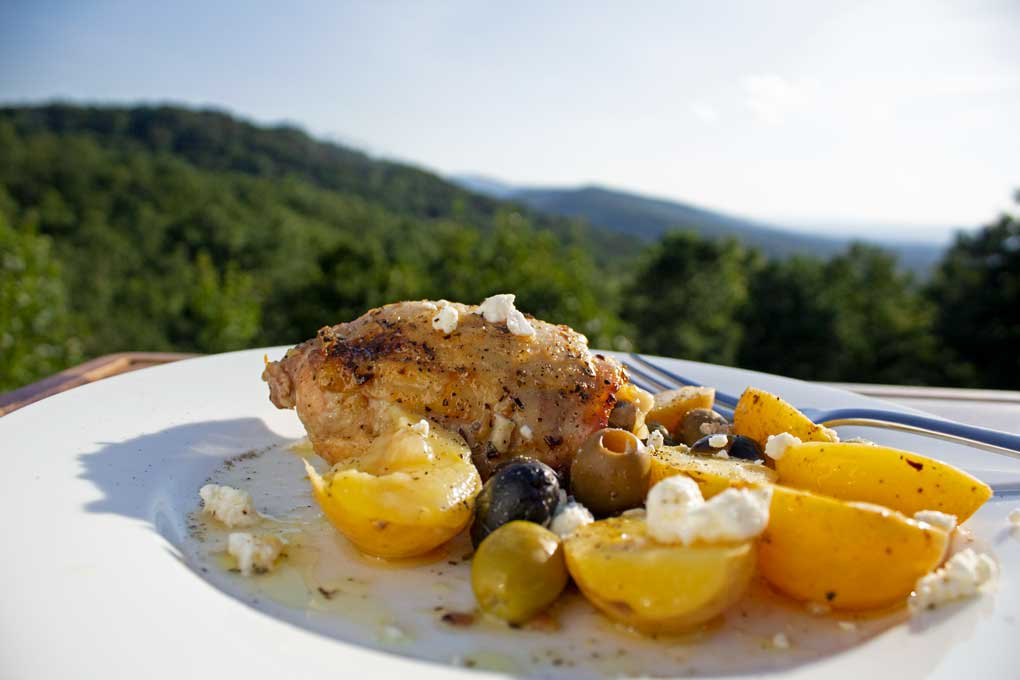 greek-style lemon garlic chicken on plate with mountain view