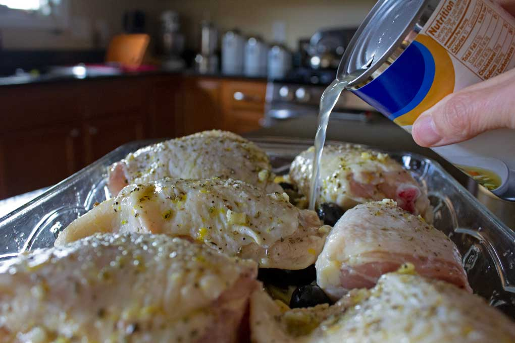pouring chicken broth into casserole dish