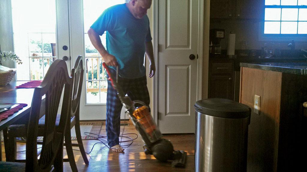 David vacuuming the house