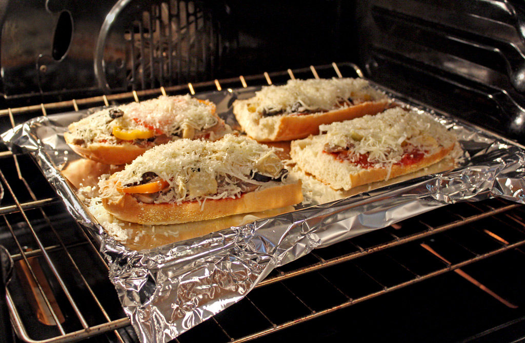 Vegetable French bread pizzas baking in oven