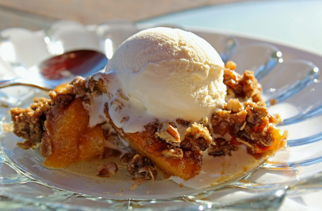David's cinnamon peach crisp is made with fresh peaches topped with crunchy rolled oats, brown sugar, pecans, and butter with warm spices. It's delicious! | TheMountainKitchen.com