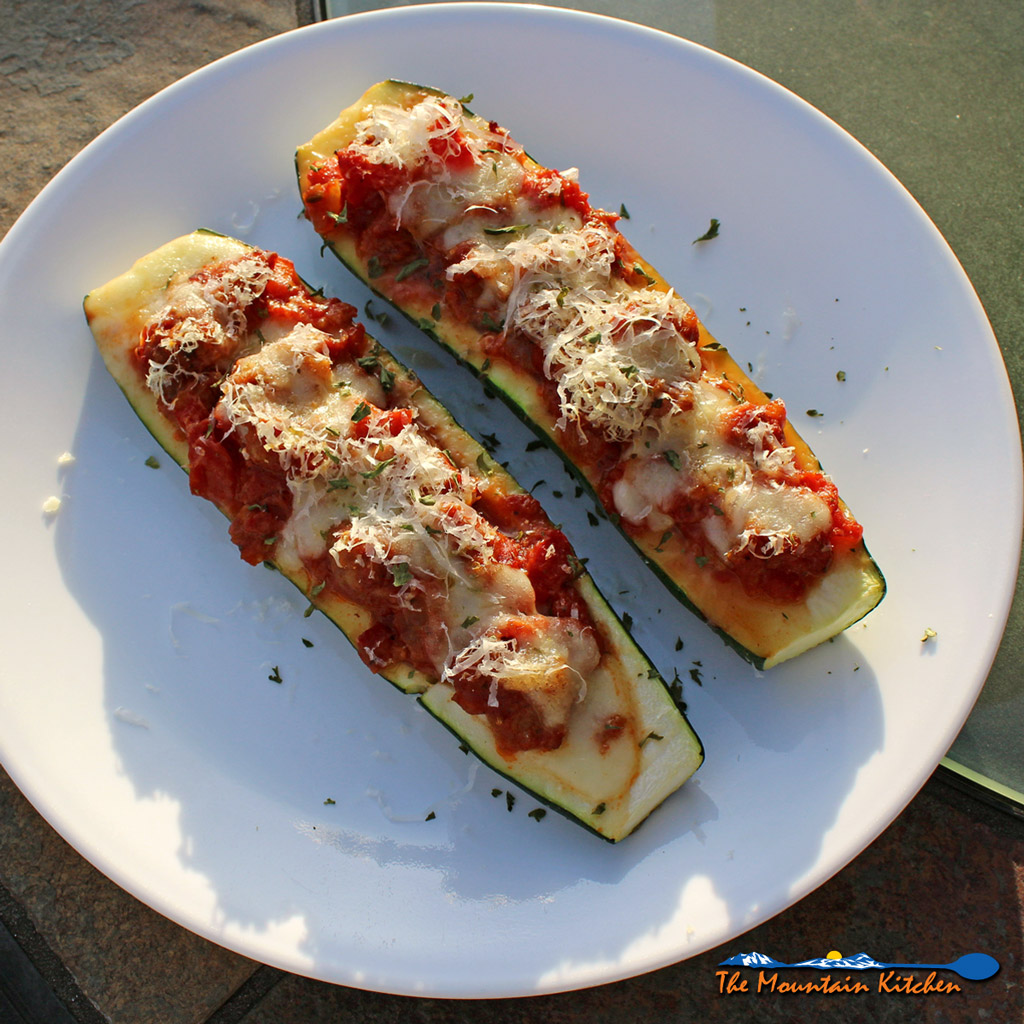 Sweet Italian sausage stuffed zucchini boats, stuffed with cheese and Italian sausage filling with diced tomatoes and herbs, piled high with more cheese!