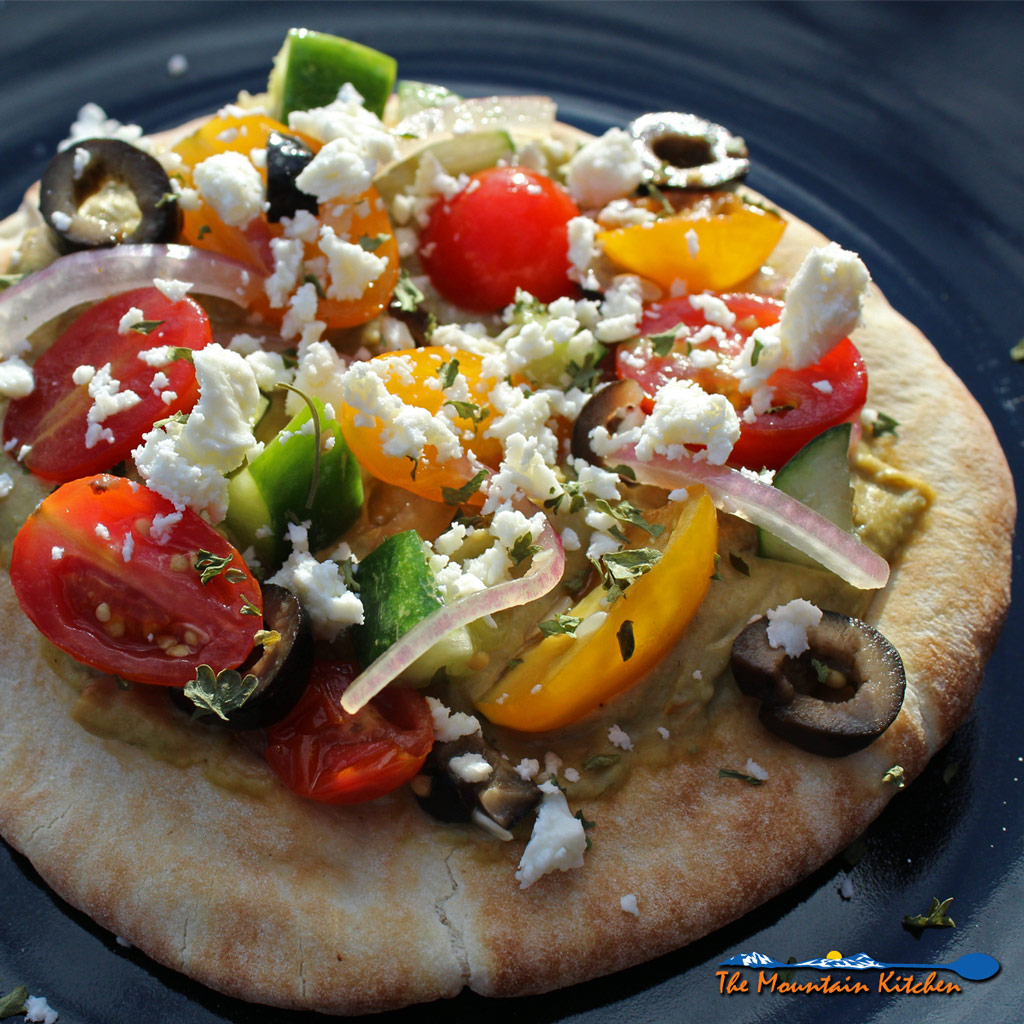 These No-Bake Greek Pizzas are made with pita bread topped with hummus, Greek salad and feta cheese. A really quick easy and healthy Meatless meal. | TheMountainKitchen.com