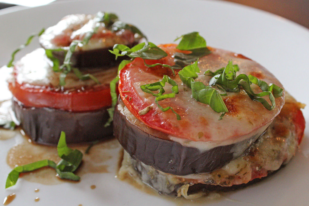 Roasted Eggplant Caprese Stacks are made with fresh basil, melted mozzarella, roasted tomatoes and eggplant slices, drizzled with balsamic vinegar read to eat